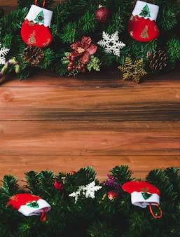 Kerstdecoratie op houten achtergrond met kopieerruimte, pijnboomtakken, kerstsokken en verschillende soorten ornamenten rekwisieten genomen van hoog boven de kijkhoek.