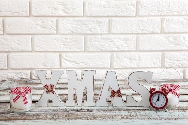 Kerstdecoratie op tafel in de buurt van witte bakstenen muur