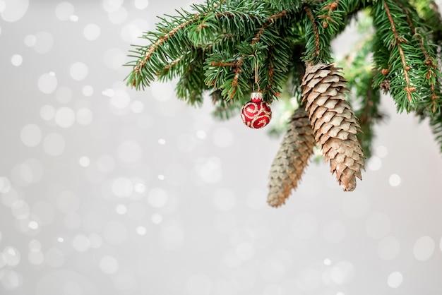 Kerstdecoratie rand gemaakt van vuren takken, fir kegels en rode glanzende ballen op luchtige bokeh lichte achtergrond