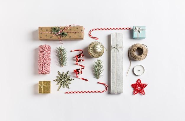 Kerstdecoratie samenstelling geschenkdoos bal vuren takken kaars lint snoepgoed