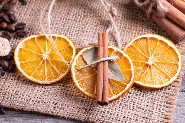 Kerstdecoratie, sinaasappelschijfje, kaneel op rustieke tafel