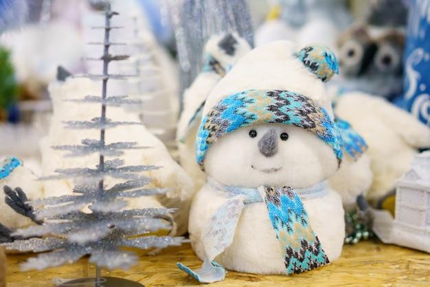 Kerstdecoratie speelgoed witte sneeuwpop gemaakt van watten met een blauwe sjaal, op de plank in de winkel
