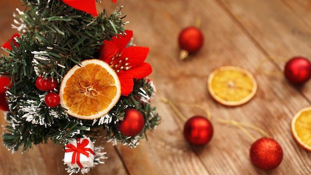 Kerstdecoratie tegen houten onscherpe achtergrond met kerstboom, gedroogde vruchten