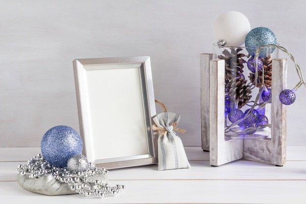 Kerstdecoratie wit frame mockup kerstballen blauwe slinger op een witte tafel kopieerruimte