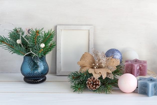 Kerstdecoratie wit frame mockup met een boeket van sparren en kerstballen op een witte tafel