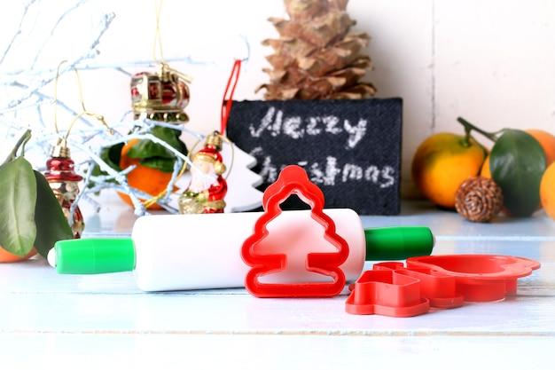 Kerstdecoratiehulpmiddelen voor het bakken van koekjes vormen een deegroller op een lichte houten achtergrond, selectieve zachte focus rustieke stijl