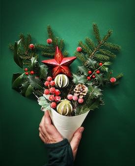 Kerstdecoraties, dennentakken, bessen, hulst, droge limoen en ster in kegel in de hand gehouden, plat liggen