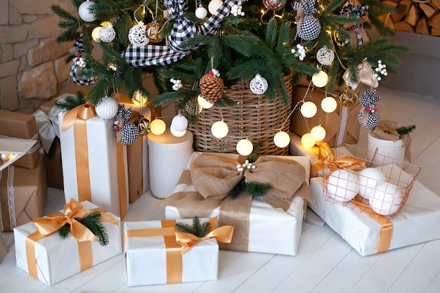 Kerstdecoraties en slingers op kerstboom thuis in rustieke stijl. de mooie dozen van de kerstmisgift op vloer dichtbij kerstboom in woonkamer. xmas geschenkdozen met decoraties. nieuwjaar