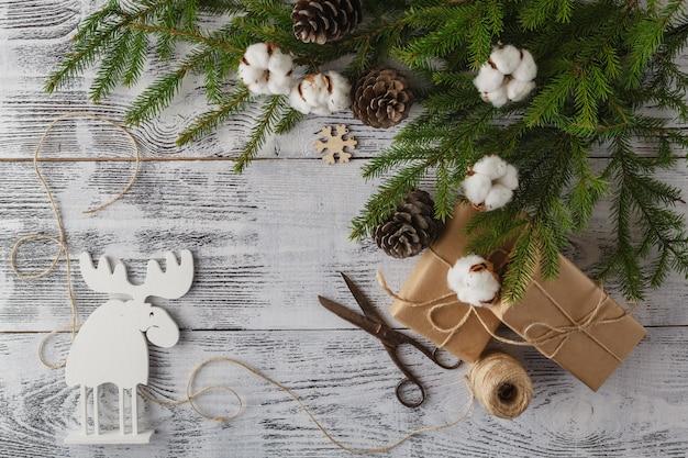 Kerstdecoraties, geschenkdozen, lint en gemberbrood op houten bord.