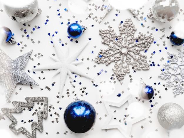 Kerstdecoraties glanzende sterren, ballen, sneeuwvlokken, confetti en gloeilampen.