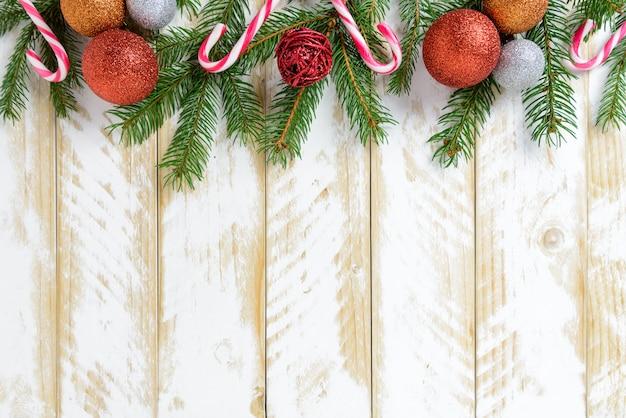 Kerstdecoraties, kleurenballen en snoepriet op een witte houten tafel. bovenaanzicht, kopie ruimte.