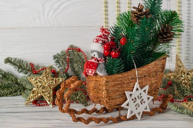 Kerstdecoraties met slee, pinguïn, dennenappels, spuce boomtakken en houten sneeuwvlok.