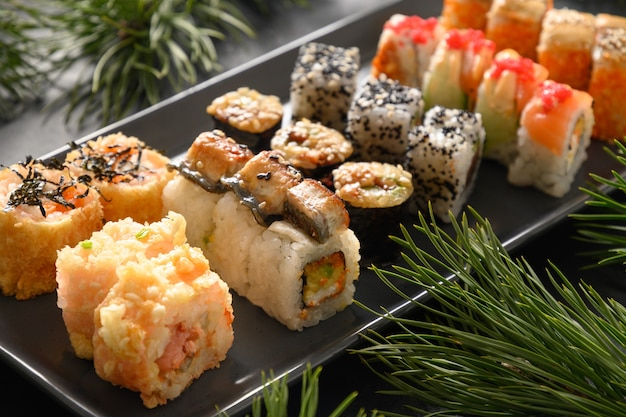 Kerstdiner met sushi set met decoratie van kerstmis op zwarte achtergrond. detailopname. kerst- of nieuwjaarsfeest.