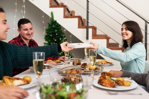 Kerstdiner thuis gelukkig lachende blanke vrouwen laten wat hapjes voorbijgaan vakantie