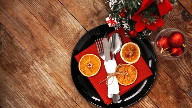 Kerstdinerdecoratie met gedroogde sinaasappels en een rood servet op een zwarte plaat
