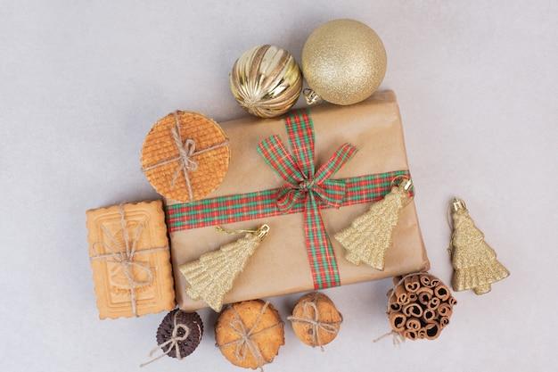 Kerstdoos met koekjes, wafels en kaneelstokjes in touw