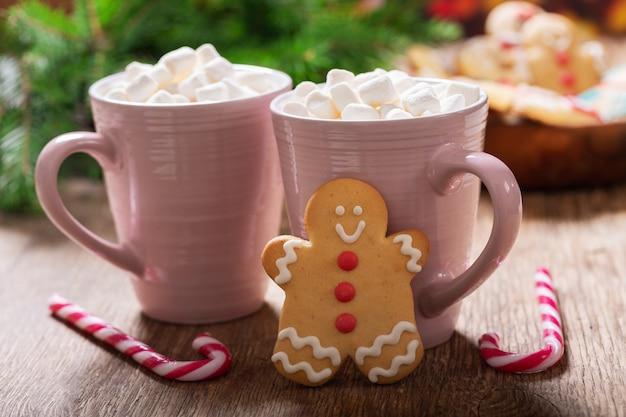 Kerstdrank kopjes warme chocolademelk met marshmallows en peperkoekkoekjes