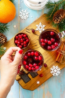 Kerstdrankjes warme winterdrank met veenbessen en kaneel op houten tafel bovenaanzicht