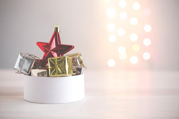 Kerstelementen in witte doos op achtergrond van gekleurde lichten ongerichtfocus