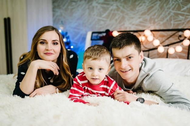 Kerstfamilie! gelukkige moeder, vader en zoontje in santa claus-truien, liggend. genieten van liefdesknuffels, vakantiemensen. vrolijk kerstfeest