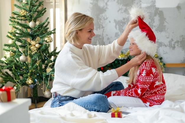 Kerstfamilie voorbereiden en gefeliciteerd. gelukkige glimlachende europese blonde moeder en dochter thuis in kerstmanhoed