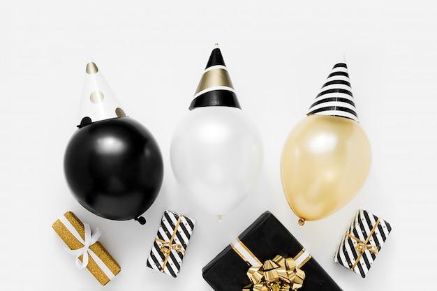 Kerstfeest concept. witte, zwarte en gouden ballonnen in feestmutsen op witte achtergrond. gelukkig nieuwjaarsviering