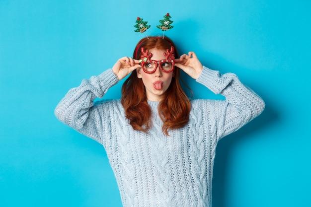 Kerstfeest en feest concept. dom roodharig meisje dat van nieuwjaar geniet, grappige glazen en hoofdband draagt, tong toont en naar links staart naar logo, blauwe achtergrond.