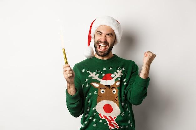 Kerstfeest en vakantie concept. gelukkige jonge man die nieuwjaar kerstmis viert, een sterretje vasthoudt en er opgewonden uitziet, staande op een witte achtergrond