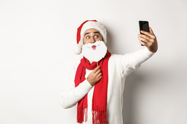 Kerstfeest en viering concept. jonge man die selfie neemt met een grappig wit baard-kerstmasker en hoed, poseren voor foto op mobiele telefoon, studio-achtergrond