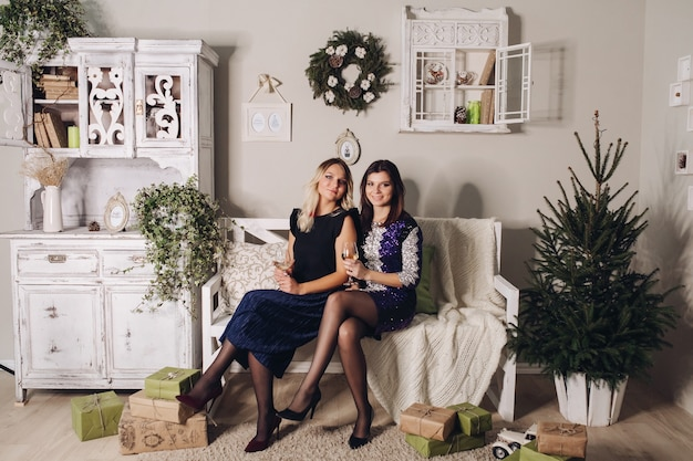 Kerstfoto's van mooie vriendinnen in avondjurken worden omringd door cadeautjes