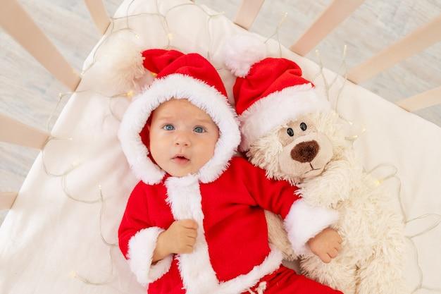Kerstfoto van een baby in een kerstman kostuum liggend in een wieg thuis met een stuk speelgoed in een kerstman hoed