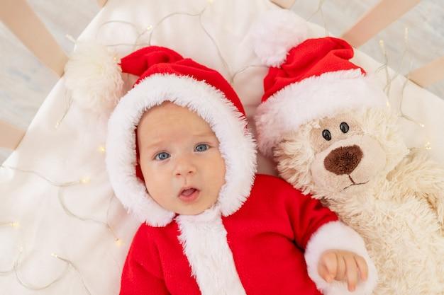 Kerstfoto van een baby in een kerstman kostuum liggend in een wieg thuis