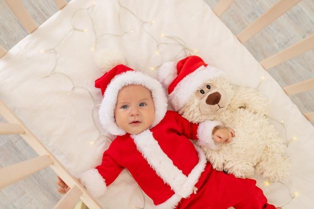 Kerstfoto van een baby in een kerstman kostuum