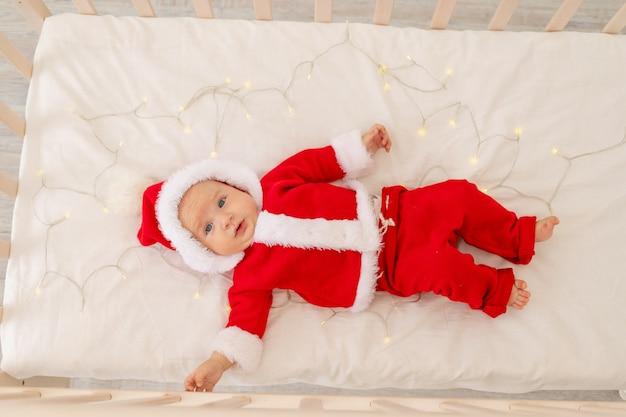 Kerstfoto van een baby in een santa-pak liggend in een wieg thuis, bovenaanzicht, gelukkig nieuwjaar.