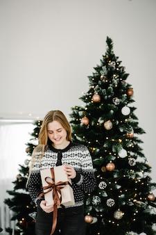 Kerstfoto van een meisje met blond haar in gezellige kleren die bij de kerstboom poseert met een cadeaudoosje