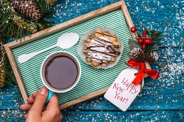 Kerstfoto van thee, cake op tafel met vuren takken, hand, ansichtkaarten