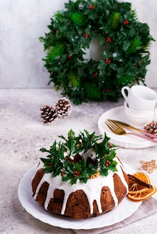 Kerstgebakken donkere chocolade bundt cake versierd met wit suikerglazuur en hulstbessentakken op een licht beton