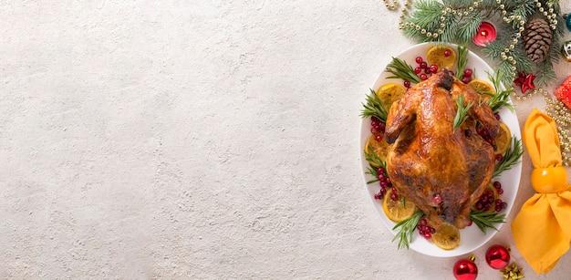 Kerstgebakken kip is feestelijk versierd met kaarsen.
