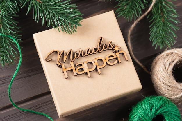 Kerstgeschenkdoos met houten letters er gebeuren wonderen. ideeën voor het inpakken van geschenken. natuurlijk design. stap voor stap
