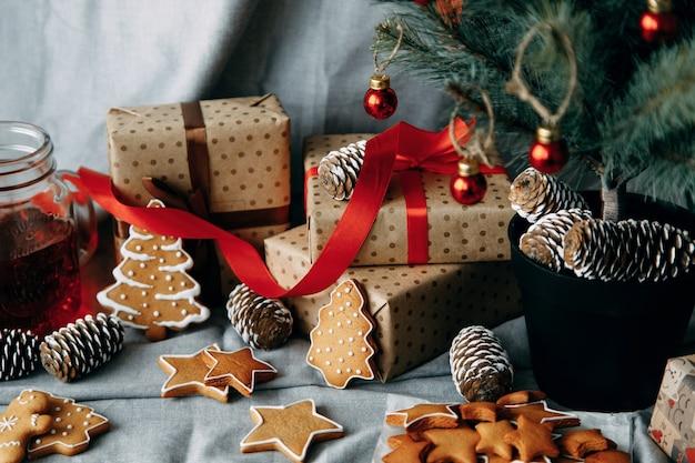 Kerstgeschenkdozen onder de kerstboom opstelling van geschenken met dennenappels en koekjes