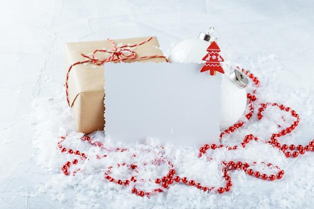 Kerstgeschenkdozen van kraftpapier, rode kralen en een felicitatiehaak op een met sneeuw bedekt oppervlak