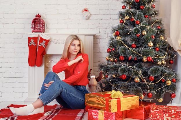 Kerstgevoel. na het kerstfeest. meisjes met blije gezichten in de buurt van de kerstboom op houten muur.