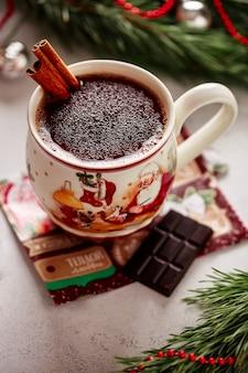Kerstglas met warme chocolademelk en noten, een takje kaneel en chocolade op een vintage servet met pijnboomtakken