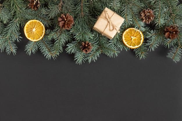 Kerstgrens met dennentakken, kegels en geschenkdozen op een zwarte achtergrond.