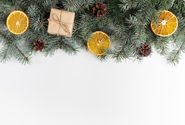 Kerstgrens met dennentakken, kegels, geschenken en gedroogde sinaasappelen op een witte achtergrond.