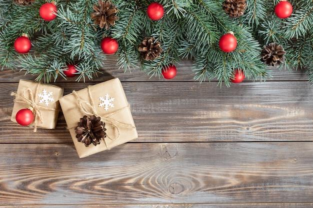 Kerstgrens met dennentakken, rode ballen en kegels op een houten ondergrond.