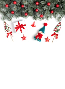Kerstgrens met dennentakken, sneeuwpoplolly's en kerstversieringen op een wit