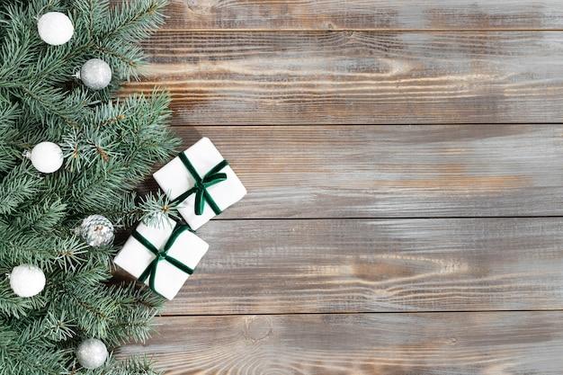 Kerstgrens met dennentakken, zilveren ballen op een houten ondergrond.