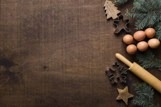 Kerstgrens met ingrediënten voor het bakken van peperkoekkoekjes versierd groenblijvende takken en koekjesmessen op houten ruimte