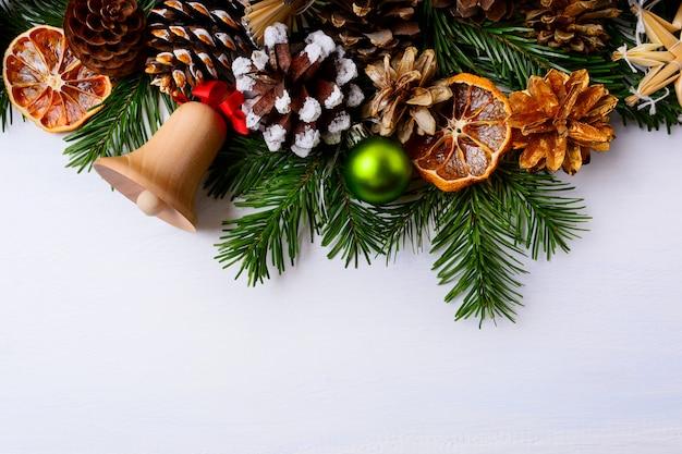 Kerstgroet met jingle bell, gedroogde sinaasappels en groen ornament